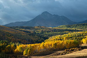 Storm clouds create dramatic lighting over fall colors Colorado