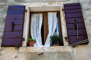 Curtains billowing through open window in Croatian town