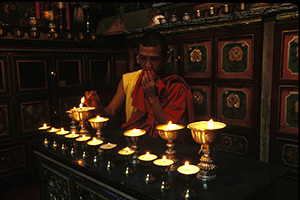 Monk lighting candles in temple